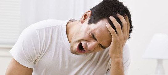 Man is experiencing headache, as a result of pressure. He's a young teacher and struggles in the job. The pain is illustrated by his painfull grimace