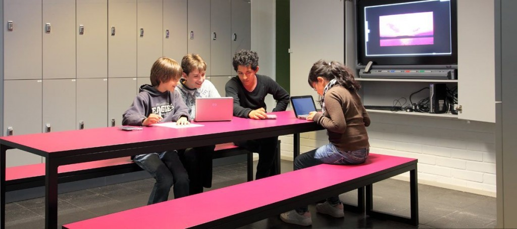 Children are sitting in a hall, working on computers. The benches are red and we can see another big screen in the background.
