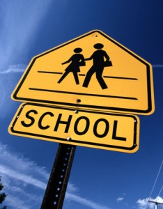school sign , yellow sign with black letters and a picture of children walking across the street